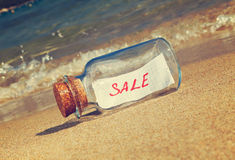 Message in a vintage bottle Sale on beach Royalty Free Stock Photography