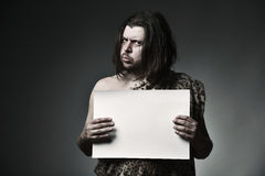 Message. Wild man neanderthal in leopard skin hold empty paper sheet Royalty Free Stock Images