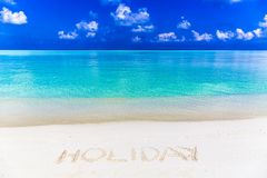 Message written on Sand. Word holiday written on sand in Maldives with the lagoon at background Royalty Free Stock Images