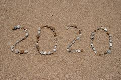 2020 year composed of colored sea stones over sand royalty free stock photo