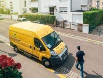 Messager d'homme marchant vers le fourgon de livraison de jaune de courrier de La Photo libre de droits