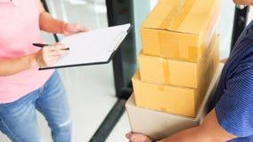 Messager de femme tenant un courrier d'expédition de colis apposant la signature photographie stock libre de droits