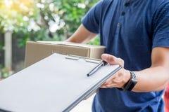 Messager de femme tenant un courrier d'expédition de colis apposant le bulletin de livraison de signature de signature après réce photos stock
