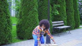 Messager de jeune femme d'Afro-américain ou livreur positif avec l'échec africain de boîte de baisses de coiffure banque de vidéos