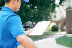 Messager de service de distribution se tenant devant la maison avec des bo?tes photos stock