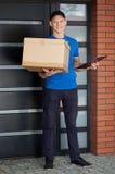Messager de sourire tenant la boîte en carton photo libre de droits