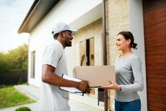 Messager Delivery Homme fournissant le paquet à la femme à la maison photo libre de droits