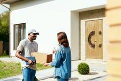 Messager Delivery Homme fournissant le paquet à la femme à la maison photo stock