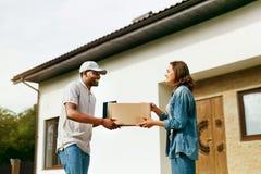 Messager Delivery Homme fournissant le paquet à la femme à la maison photos libres de droits