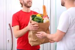 Messager donnant le sac de papier avec des produits au client à la maison, plan rapproché La livraison de nourriture image libre de droits