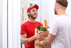 Messager donnant le sac de papier avec des produits au client à la maison photo libre de droits