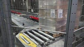 Messager emballé sur la chaîne de production contre des boîtes en carton dans l'entrepôt clip Boîtes en carton sur la bande de co banque de vidéos