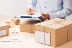Messager faisant des notes dans le reçu de la livraison parmi des colis à la table image stock