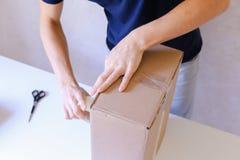 Messager Manstanding dans le bureau de poste, boîte de Brown de bande de colle sur tout le S Images stock