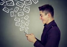 Messages de envoi occupés d'homme au téléphone intelligent Photographie stock libre de droits