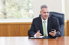 Messaggi di testo della lettura dell'uomo d'affari sul suo telefono Immagini Stock