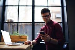 Messaggi di testo maschii seri bei della lettura delle free lance che controllano email su cellulare Immagini Stock Libere da Diritti
