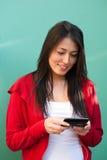 Messaggi texting della giovane donna sul telefono mobile Fotografie Stock Libere da Diritti