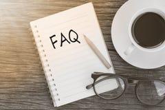 Messaggio del FAQ di concetto sul taccuino con i vetri, la matita ed il caffè Immagine Stock