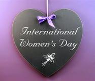 Messaggio del giorno delle donne internazionali scritto sulla lavagna di forma del cuore Fotografia Stock