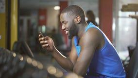 Messaggio di battitura a macchina del giovane sullo smartphone con il sorriso sul fronte, rottura durante l'allenamento stock footage