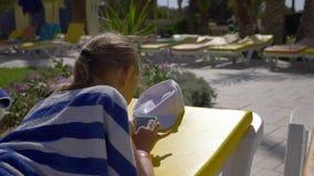 Messaggio di battitura a macchina dell'adolescente della ragazza sul telefono cellulare durante il sunbath sulle chaise longue archivi video