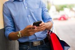 Messaggio di battitura a macchina dell'uomo afroamericano sui sacchetti della spesa del telefono Fotografia Stock