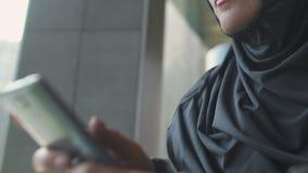 Messaggio di battitura a macchina della donna musulmana pensierosa sul telefono, prendente decisione seria, primo piano archivi video