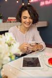 Messaggio di battitura a macchina della giovane ragazza graziosa sul telefono cellulare Immagine Stock