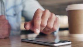 Messaggio di battitura a macchina della mano maschio sul telefono cellulare sulla tavola video d archivio