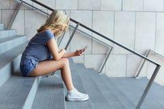 Messaggio di battitura a macchina della ragazza sul telefono cellulare e sedersi sulle scale Immagini Stock