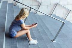 Messaggio di battitura a macchina della ragazza sul telefono cellulare e sedersi sulle scale Fotografie Stock