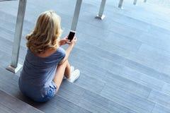 Messaggio di battitura a macchina della ragazza sul telefono cellulare e sedersi sulle scale Fotografia Stock Libera da Diritti