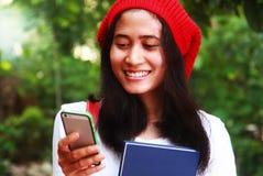 Messaggio di battitura a macchina della studentessa sul telefono Fotografia Stock Libera da Diritti