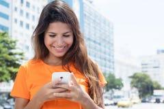 Messaggio di battitura a macchina di risata della donna caucasica con il telefono Immagine Stock Libera da Diritti