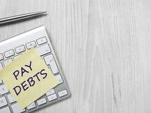 Messaggio di debiti di paga sulla nota adesiva immagine stock