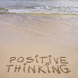 Messaggio di pensiero positivo scritto sulla sabbia, con le onde nel fondo Fotografie Stock Libere da Diritti