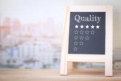 Messaggio di qualità di concetto sui bordi di legno Fotografie Stock