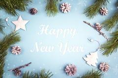 Messaggio di saluto del nuovo anno con i rami dell'abete e le decorazioni bianche sui precedenti blu fotografia stock libera da diritti
