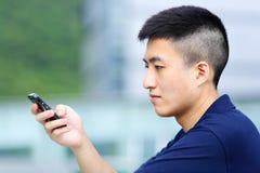 Messaggio di testo dell'uomo sul telefono Immagine Stock Libera da Diritti
