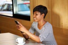 Messaggio di testo della lettura della donna sul telefono mobile Fotografia Stock Libera da Diritti