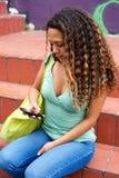 Messaggio di testo della lettura della giovane donna sul suo telefono cellulare Fotografie Stock