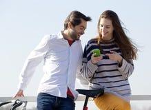 Messaggio di testo di sguardo esterno delle coppie felici sul telefono cellulare Immagini Stock Libere da Diritti
