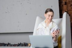 Messaggio di testo femminile allegro della lettura dell'imprenditore sul telefono delle cellule dopo webinar sul NET-libro Immagine Stock Libera da Diritti