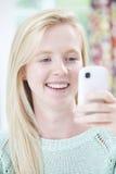 Messaggio di testo sorridente della lettura della giovane donna Immagini Stock Libere da Diritti