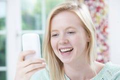 Messaggio di testo sorridente della lettura della giovane donna Fotografie Stock Libere da Diritti