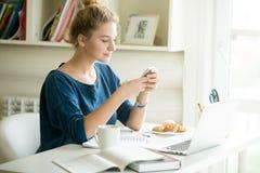 Messaggio felice della donna in di casa ufficio accogliente Fotografia Stock