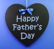 Messaggio felice di giorno di padri scritto su una lavagna del nero di forma del cuore Fotografia Stock