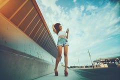 Messaggio mandante un sms della ragazza al suo amico negli ambienti urbani Fotografia Stock