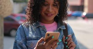 Messaggio multirazziale della lettura della donna in telefono con la risata in città